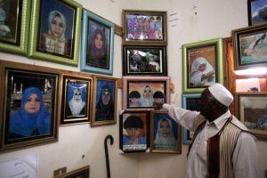 XXXII 4 - Un Libyen devant les photos des victimes tuées par les propagandistes puants de la fausse démocratie occidentale