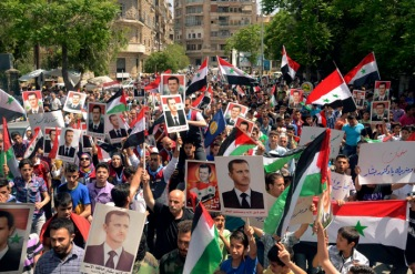 Supporters of Syria's President Bashar al-Assad take part in a rally showing support a day after he declared that he would seek re-election in June, in Aleppo April 29, 2014. Al-Assad declared on Monday he will seek re-election in June, defying calls from his opponents to step aside and allow a political solution to the devastating civil war stemming from protests against his rule. REUTERS/George Ourfalian (SYRIA - Tags: POLITICS ELECTIONS) - RTR3N3ED
